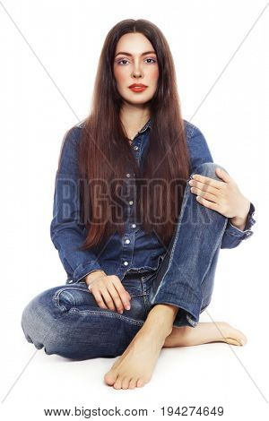 Young beautiful girl in jeans sitting over white background