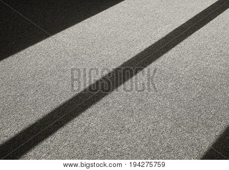 Shadow by incident light on a carpet floor in front of a window