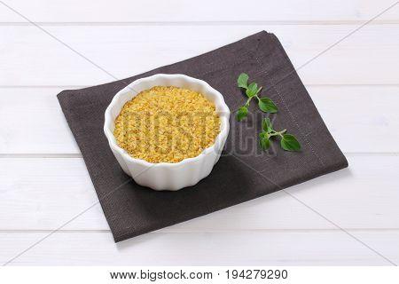 bowl of dry wheat bulgur on dark grey place mat