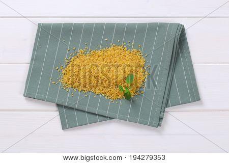 pile of dry wheat bulgur on grey place mat