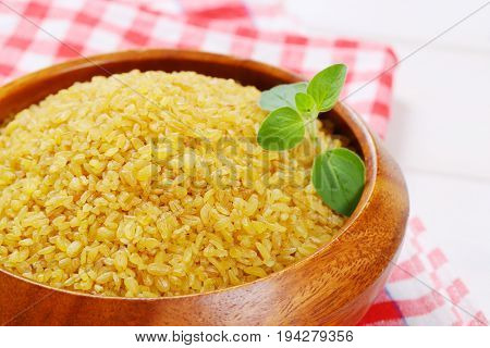 bowl of dry wheat bulgur on checkered dishtowel - close up