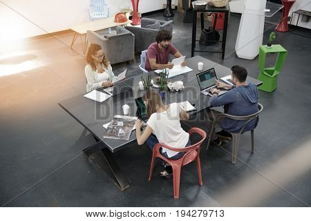 Upper view of start-up people working in open co-working office