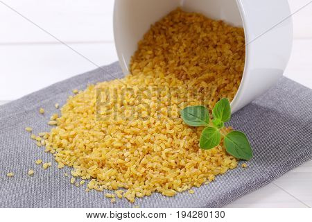 bowl of dry wheat bulgur spilt out on grey place mat - close up