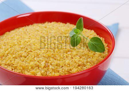 bowl of dry wheat bulgur on blue place mat - close up