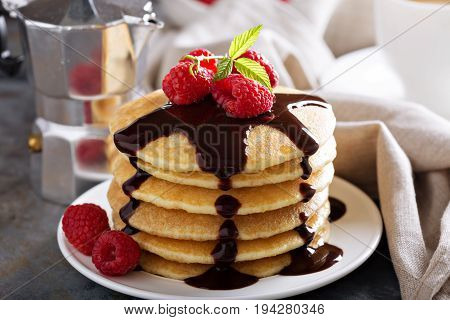 Stack of fluffy buttermilk pancakes with chocolate syrup and raspberries