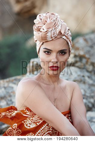 Portrait of young beautiful brunette woman with stylish make-up and colorful oriental scarf on her head