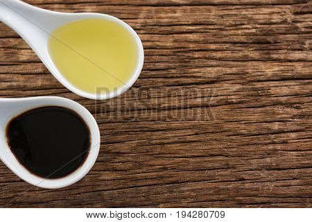 Close-up of olive oil and balsamic vinegar in spoon on table