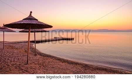 View on the beach Moraitika with sun umbrellas on the sunrise on the the island Corfu Greece.
