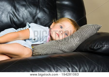 2 year old girl in blue pyjamas lying on the couch daydreaming