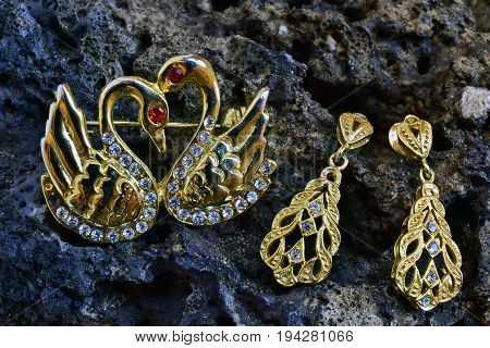 Brooch and gold earrings on a stone