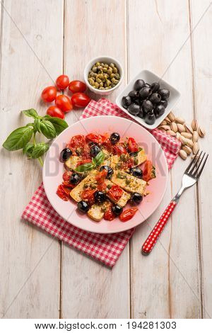 tofu salad with tomatoes black olives capers and pistachio