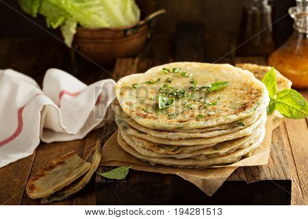 Stack of fried green onion pancakes on a wooden board
