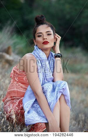 Fashion portrait of beautiful sexy female brunette girl model sitting in green summer bright grass in the park with make-up in oriental scarf.perfect skin.nature