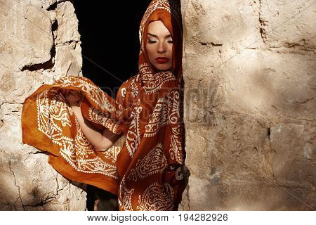 A beautiful young Muslim woman in Islamic clothes looks so sad when one hand is standing in the doorway of a brick destroyed house