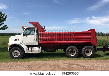 Red and white dump truck against a blue summer sky