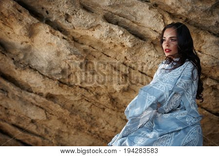 Young sexy oriental lady with colorful scarf posing in mountain. Dark haired brunette with amazing make-up.
