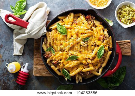 Cheesy pasta bake in a pan with ground beef and herbs overhead shot