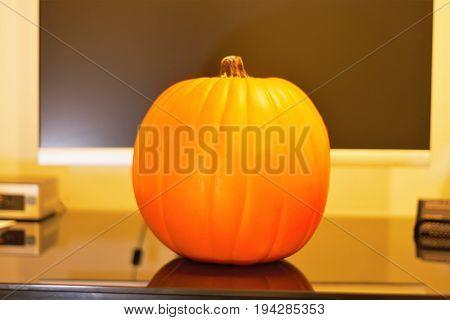 Pumpkin sitting on desk with computer moniter