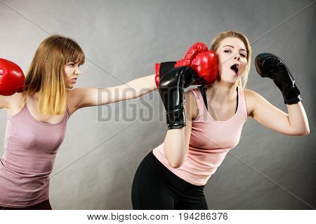 Agressive women having argue fight wearing boxing gloves female friend being scared. Violance concept.