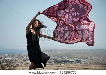 Beautiful girl with dark hair woman model in elegant black dress standing on rock with flying in the wind long tulle silk chiffon scarf on sea and sky background