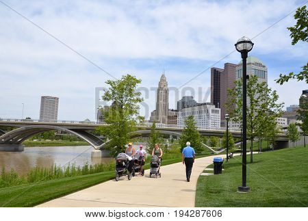 COLUMBUS OH - JUNE 28: Walkers on the Scioto Mile in downtown Columbus Ohio are shown on June 28 2017.