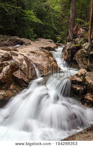 River flows down rocky bed  creating Waterfall flowing over rocks in The Basin New Hampshire on a summer day