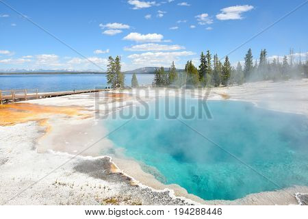 YELLOWSTONE NATIONAL PARK, WYOMING - JUNE 25, 2017: Tourists Black Pool, a hot spring in the West Thumb Geyser Basin. Extremely hot, and one of the parks most beautiful and intense blue pools.