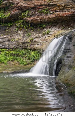 A small waterfall spills from a narrow rocky ravine on the Hocking River at Rock Mill in Fairfield County Ohio.