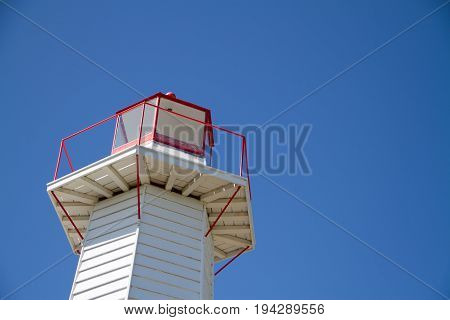 Lantern on a hexagonal white lighthouse or pharos for marine navigation and to warn of hazards such as rocks and shoals viewed close up from below against a blue sky