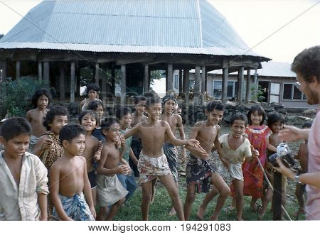 SAVAI'I / SAMOA - CIRCA 1990: Samoan children are entertained by an American tourist with a camera.