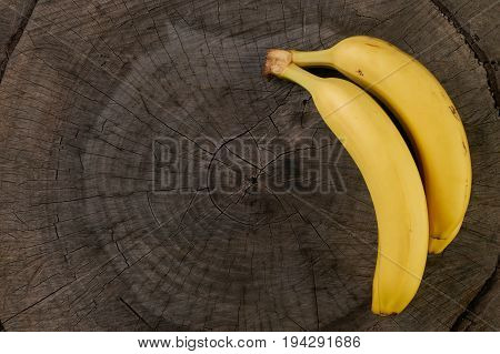 Banana. Ripe banana isolated on wooden background with copy space. Top view close-up.