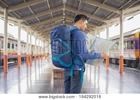 man traveler with backpacker look searching location at trainstation travel concept