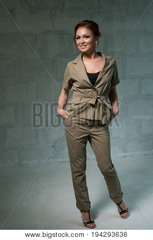 Beautiful brown haired woman in nice khaki jacket and pants posing in studio with charming smile
