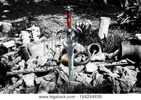 An ancient sword and a dagger on a natural landscape with stones and clay jugs.