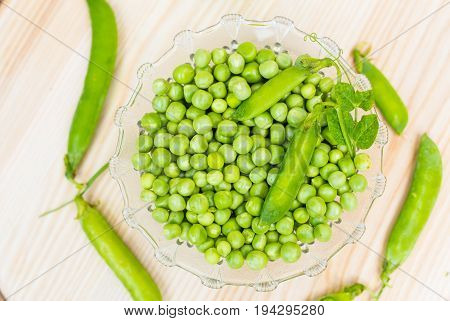 Fresh green peas on a plate. Light wooden background