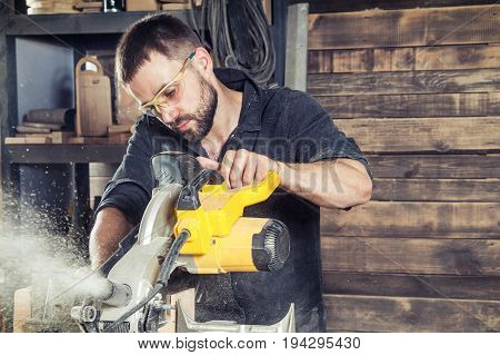 A young male construction carpenter saws a modern circular saw with a wooden board in the workshop a wooden sawdust flying into the sides