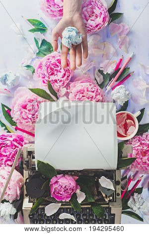 A hand holding a paper ball above writer's workplace with typewriter, stationery, crumpled paper and pink peony flowers