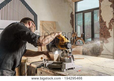 A young male construction carpenter saws a modern circular saw with a wooden board in the workshop room a wooden sawdust fly to the sides a rear view sideways