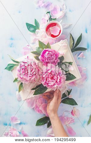 Reader's hand holding an open book with pink peony flowers on a light wooden background