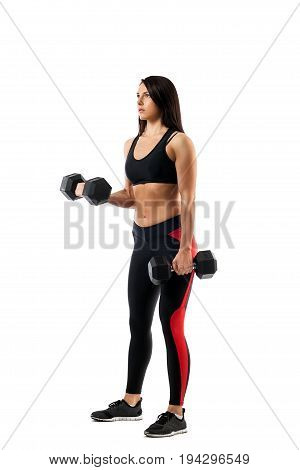 Young athletic woman fitness model doing an exercise with dumbbells on the biceps one arm in the position underneath the second in a bent state on a white isolated background