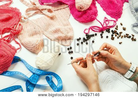 A young woman knits a crochet on a table with a lot of threads wares beads ribbons