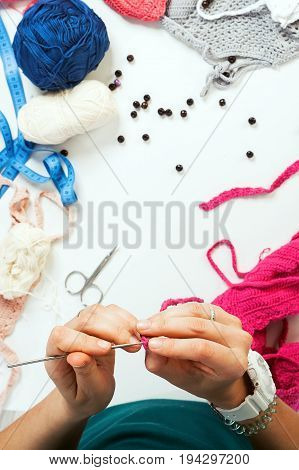 Close-up of knitting against a background of beads threads knitting needles products from natural wool on a working female table