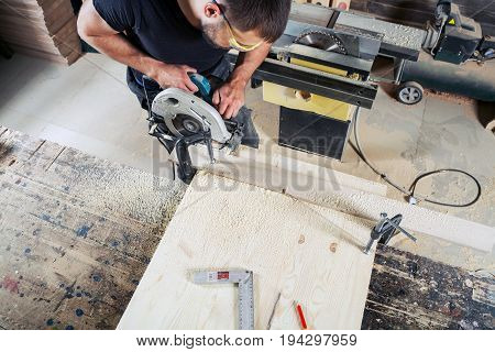 Young man builder carpenter sawing wooden dosal circular saw in workshop top view