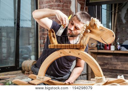 Young man builder carpenter paints children's wooden toy rocking chair in the form of a horse