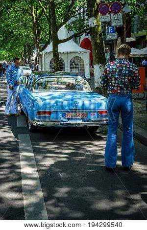 BERLIN - JUNE 17 2017: Two men dressed in the style of the 70's look at Mercedes-Benz 220 SE. Classic Days Berlin 2017.