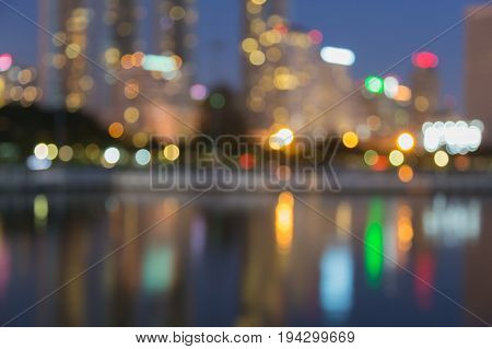 Night blurred bokeh light with water reflection city building abstract background