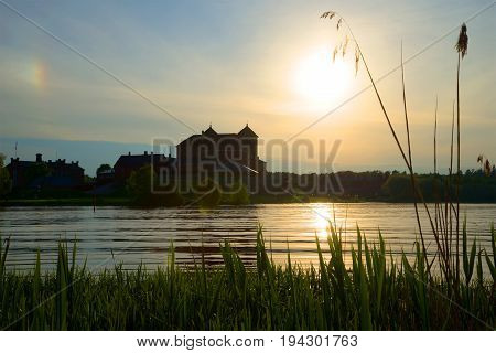 June evening on the Vanajavesi lake. View of the medieval fortress of Hameenlinna, Finland