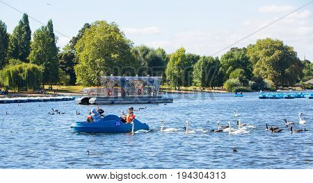 London, UK - September 8, 2016: Hyde Park featuring the Serpentine recreational lake and people having fun with pedalling boats