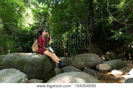 Women hikerwith backpack checks map to find directions and look binoculars in wilderness area at waterfalls and forest. Travel Concept