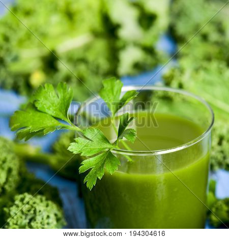 a green smoothie served in a glass topped with a twig of parsley and surrounded by kale leaves kale, on a blue rustic wooden table